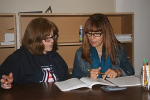 At the Language School, a  tutor helps a woman with English language skills.